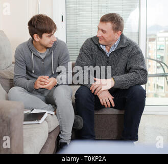 Guy with his father are resting and talking about teenage life - Stock Photo