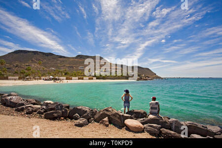 A young couple enjoy the view from a rocky jetty along the Bay of La Paz, near the city of La Paz, Baja, Mexic o - Stock Photo