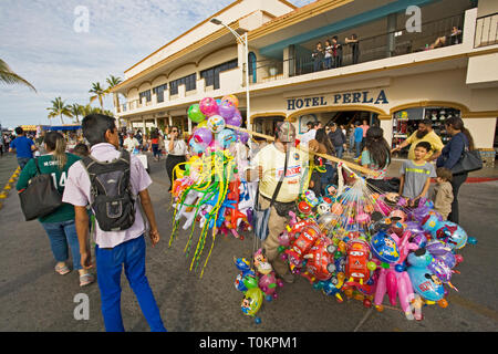 A street vendor sell balloons to children on the Malecon during the Carnival celebration in La Paz, Baja, Mexico. - Stock Photo