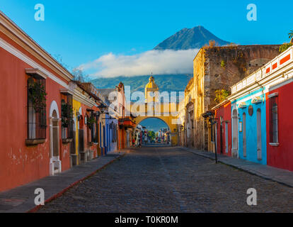 Cityscape of the main street and yellow Santa Catalina arch in the historic city center of Antigua at sunrise with the Agua volcano, Guatemala. - Stock Photo