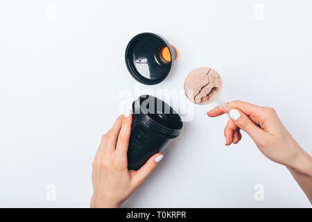 Woman's hands putting scoop of chocolate protein powder into black plastic shaker to prepare sports drink for muscle growth, top view on white table. - Stock Photo