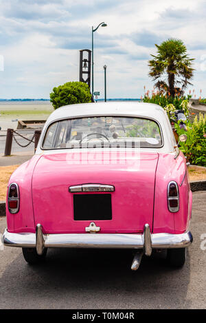 A classic pink oldtimer car parked on the coast in Cancale, Brittany, France - Stock Photo