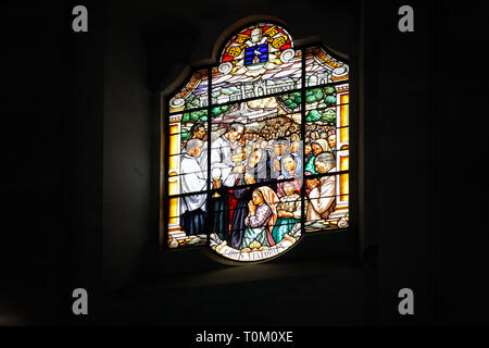 One of the stained glass windows of the basilica of Fatima representing communion in the celebrations - Stock Photo