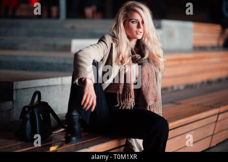 Pensive blonde sitting on bench. - Stock Photo