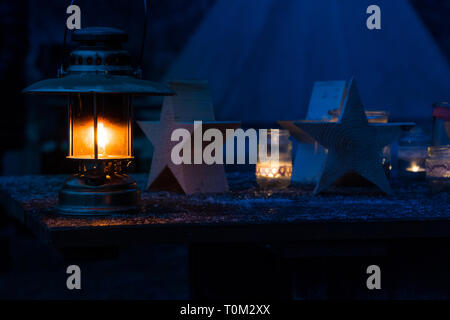 Kerosene lamp in the frosty night on the wooden table - Stock Photo