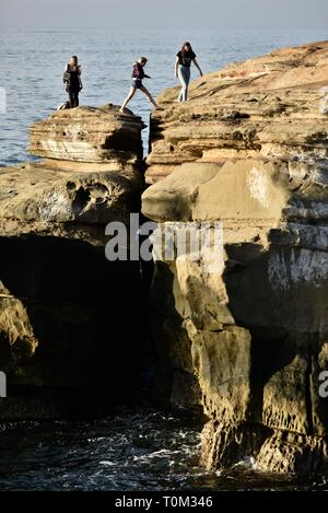 People exploring and jumping over rocky crevice on the sandstone cliffs of Sunset Cliffs, waves from Pacific Ocean, San Diego, CA, USA - Stock Photo