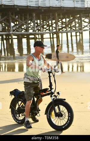 Fit, middle-aged man riding fat tire bicycle biking on beach during sunset at Pacific Beach, San Diego, California, USA - Stock Photo