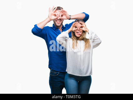 Young couple in love over isolated background doing ok gesture like binoculars sticking tongue out, eyes looking through fingers. Crazy expression. - Stock Photo