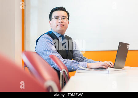 An international asian young male student sits in a classroom at a desk working and studying on his laptop in a modern classroom. - Stock Photo