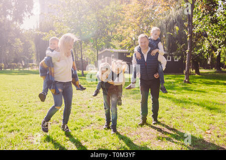 Theme family active leisure outside in nature. large Caucasian family with four children. Mom and Dad actively relaxing. enjoy life in park near house - Stock Photo