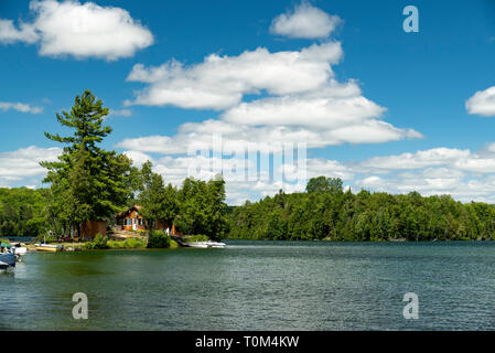 Cabin and docked motorboats on a lake in Ontario Canada's Cottage Country with clouds in a blue sky on a summer afternoon. - Stock Photo