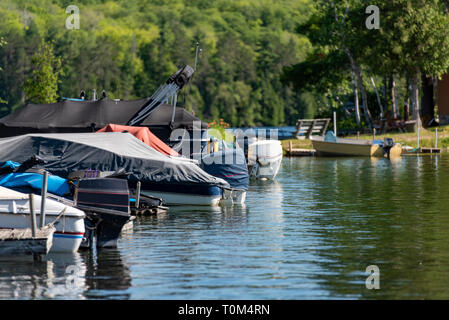 Motorboats docked on a lake in Ontario Canada's Cottage Country on a summer morning. - Stock Photo