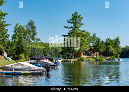 Cabin and docked motorboats on a lake in Ontario Canada's Cottage Country with a blue sky on a summer morning. - Stock Photo