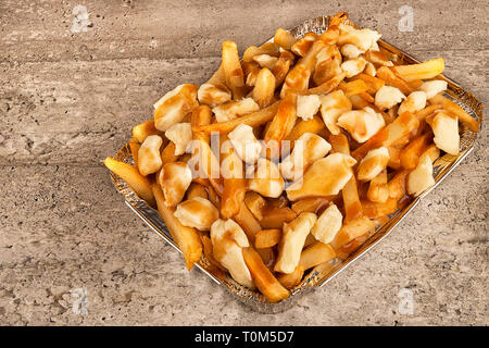 Close up on a poutine in a takeout container. Cooked with french fries, beef gravy and curd cheese. - Stock Photo