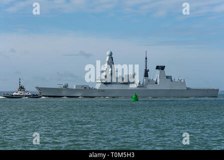 A Naval Base tug escorts the Royal Navy Type 45 destroyer HMS Defender in The Solent as the warship departs Portsmouth, UK on the 18th March 2019. - Stock Photo