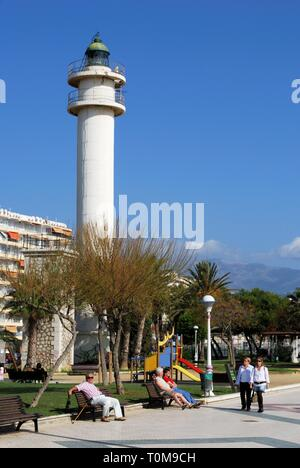 View of the lighthouse and childrens playground along the promenade with tourists enjoying the setting, Torre del Mar, Malaga Province, Andalusia, Spa - Stock Photo