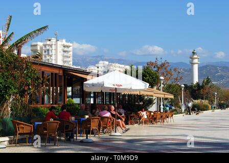 Tourists and pavement cafes along the promenade with the lighthouse to the rear, Torre del Mar, Malaga Province, Andalusia, Spain, Western Europe. - Stock Photo