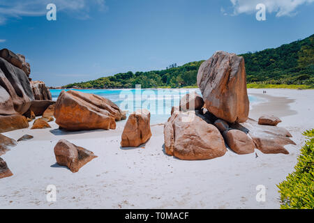 Couple on tropical beach lagoon with granite boulders in the turquoise water and a pristine white sand at Anse Cocos, La Digue island, Seychelles - Stock Photo
