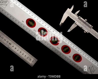 Ruler, spirit level and caliper on a black background. Cut-out. Concepts of accuracy and technic. - Stock Photo