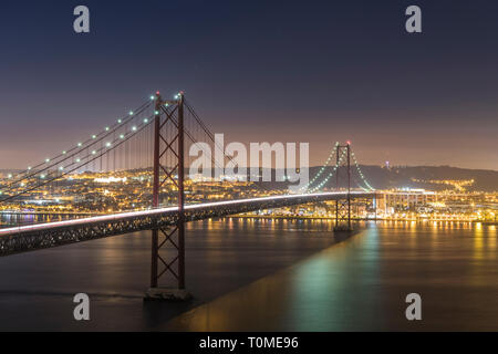 Night shot of Ponte 25 de Abril (bridge) and Lisbon, Portugal - Stock Photo