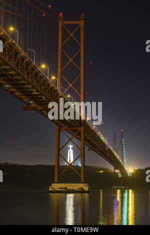 Night shot of Ponte 25 de Abril (bridge) and Cristo Rei (Christ statue in Almada), Lisbon, Portugal - Stock Photo