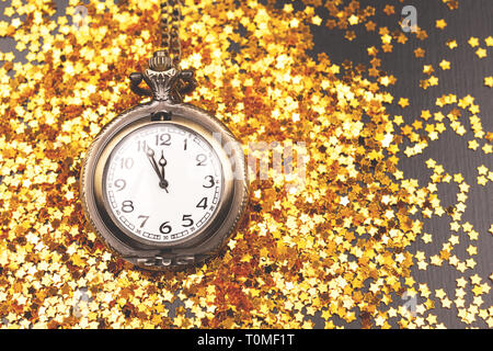Vintage clock shows almoust midnight. Decorated with confetti. New Year countdown concept. Flat-lay, top view. Copy space for your text. - Stock Photo