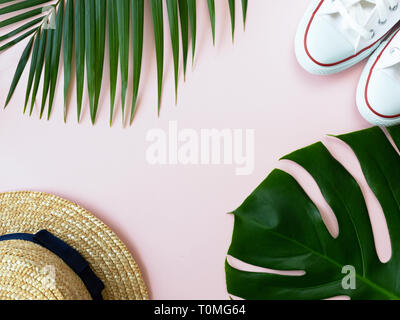 Shells, sneakers, tropical leaves and summer hat on the pink background. Minimal summer concept. Hipster vibes - Stock Photo