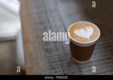 Cappuccino with beautiful heart shape latte art in the paper to-go cup. Take away coffee concept. Wooden rustic background. Copy space for your text.  - Stock Photo