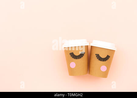 Take out coffee or tea cup on the pastel pink background. Funny closed eyes with lashes and blush made with paper. Coffee love concept. Flat-lay, top  - Stock Photo