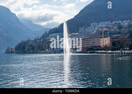 View of central Lugano with lake and fountain in March - Stock Photo