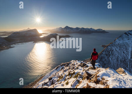 From the summit of Mannen, hiker looks out over the Lofoten landscape towards the sun, Lofoten, Nordland, Norway - Stock Photo