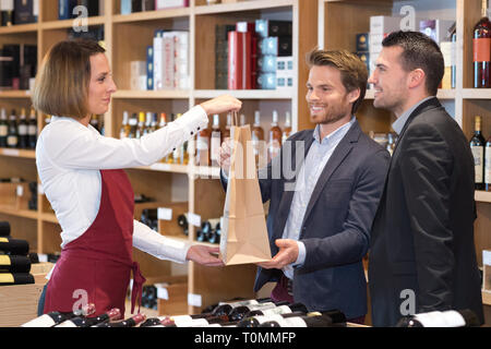 male friends buying bottles of wine in shop - Stock Photo
