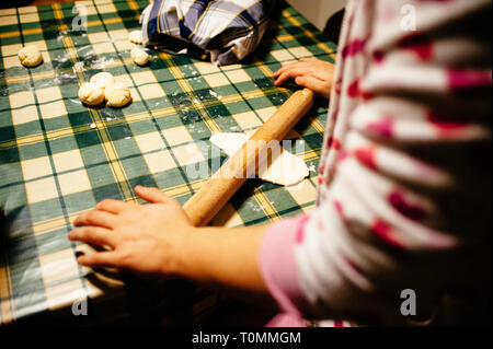 girl prepares pizza dough in the kitchen with rolling pin - Stock Photo