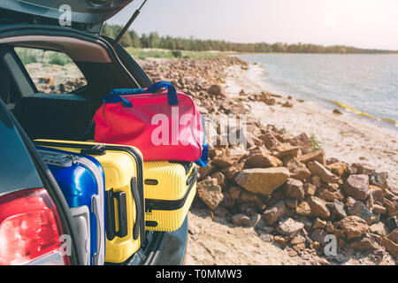 Suitcases and bags in trunk of car ready to depart for holidays. Moving boxes and suitcases in trunk of car, outdoors. trip, travel, sea. car on the b - Stock Photo