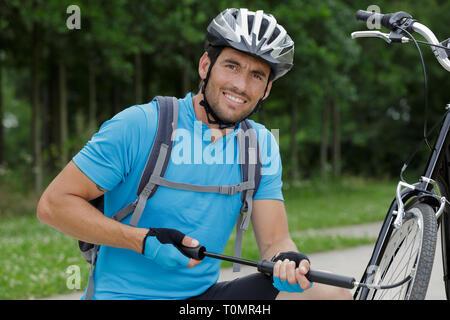 biker pausing to pump bike wheel - Stock Photo