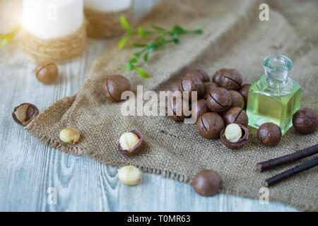 Macadam nuts, walnut oil, on wooden background. Relax, health care, body care Healthy food - Stock Photo