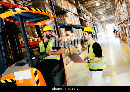 Warehouse workers working together with forklift loader - Stock Photo