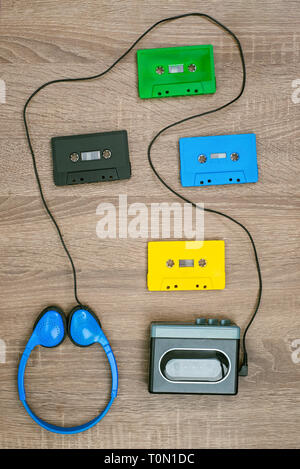Vintage cassette player, colorful cassete and headphones on the wooden background - Stock Photo