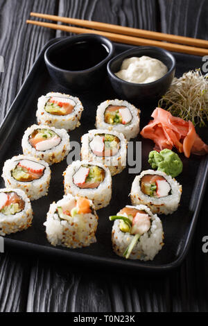 Uramaki rolls sushi served with sauces, ginger and wasabi closeup on a plate on the table. vertical - Stock Photo