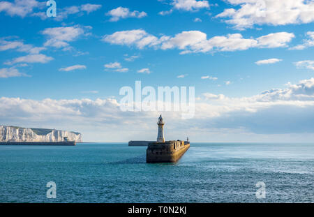 A view of the southern breakwater in the Port of Dover; with the famous White Cliffs in the background. - Stock Photo