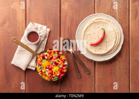 Mexican breakfast food. Huevos rancheros, baked eggs, shot from the top with pico de gallo salad, hot chocolate, and tortillas - Stock Photo
