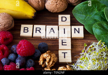 'Brain diet' words written on wooden blokcs with foods that boost brain function, memory, health and concentration - Stock Photo