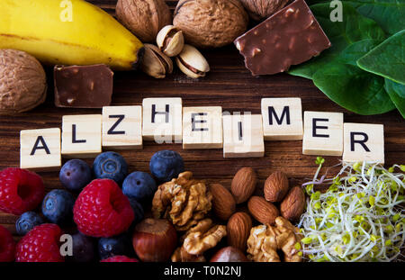 'Alzheimer' word written on wooden blocks and foods supporting the treatment of Alzheimer's Disease - Stock Photo