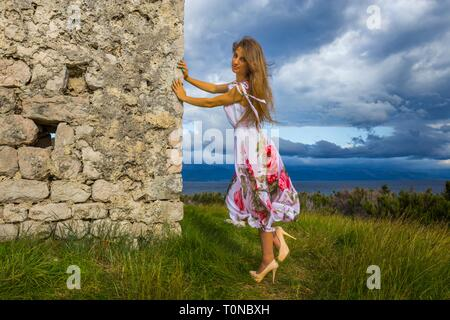 Beautiful young woman standing next to made of stone old house wearing long flowery dress and Beige colored high-heels heeled shoes stiletto pumps - Stock Photo