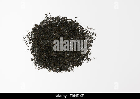 Blackseeds or Niger seeds (Guizotia abyssinica) on a white background - Stock Photo
