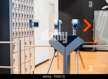 Fingerprint scanners at the entrance in modern bright gym and wooden Lockers with electronic locks on background. - Stock Photo