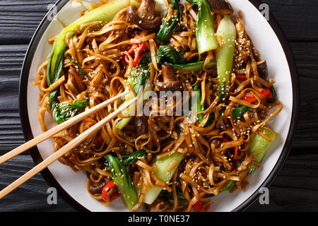 Stir fry of udon noodles with pak choi and shiitake mushrooms close-up on a plate. Horizontal top view from above - Stock Photo