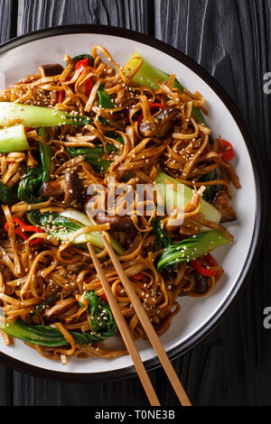 Chinese udon noodles with bok choy, shiitake mushrooms  and pepper close-up on a plate on the table. Vertical top view from above - Stock Photo