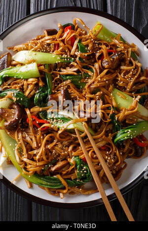 Stir fry of udon noodles with pak choi and shiitake mushrooms close-up on a plate. Vertical top view from above - Stock Photo