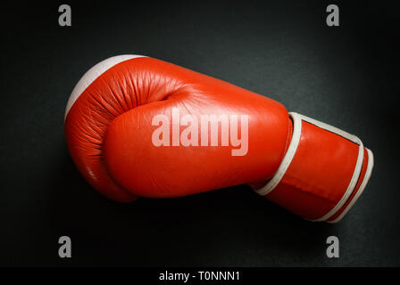 Old and used boxing glove on dark background. - Stock Photo